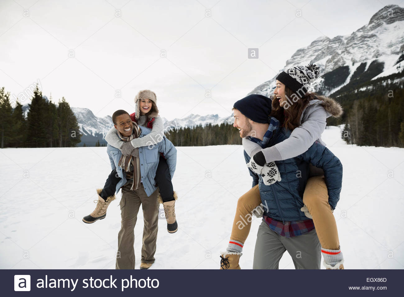 Couples piggybacking in snowy field below mountain - Stock Image