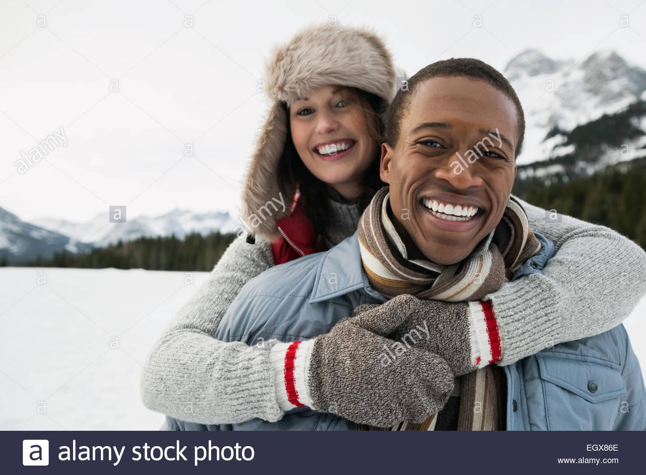 Portrait of hugging couple in snowy field Stock Photo