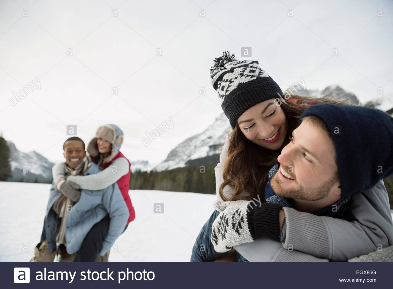 Couples piggybacking in snowy field - Stock Image