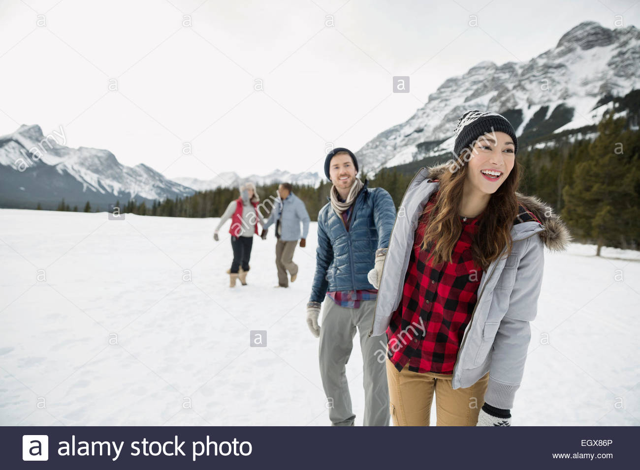 Couple holding hands in snowy field below mountains - Stock Image
