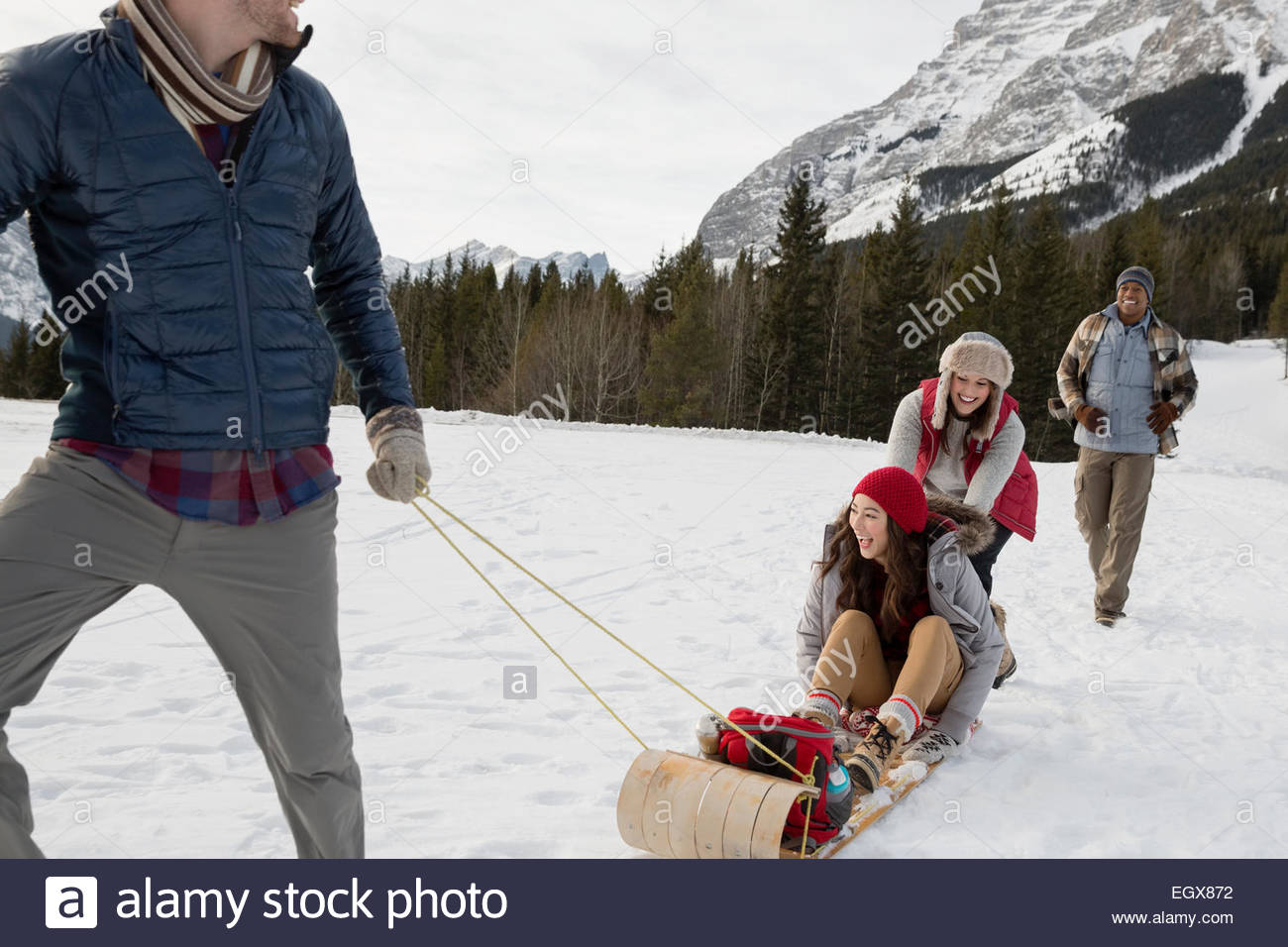 Couples sledding in snowy field below mountains - Stock Image