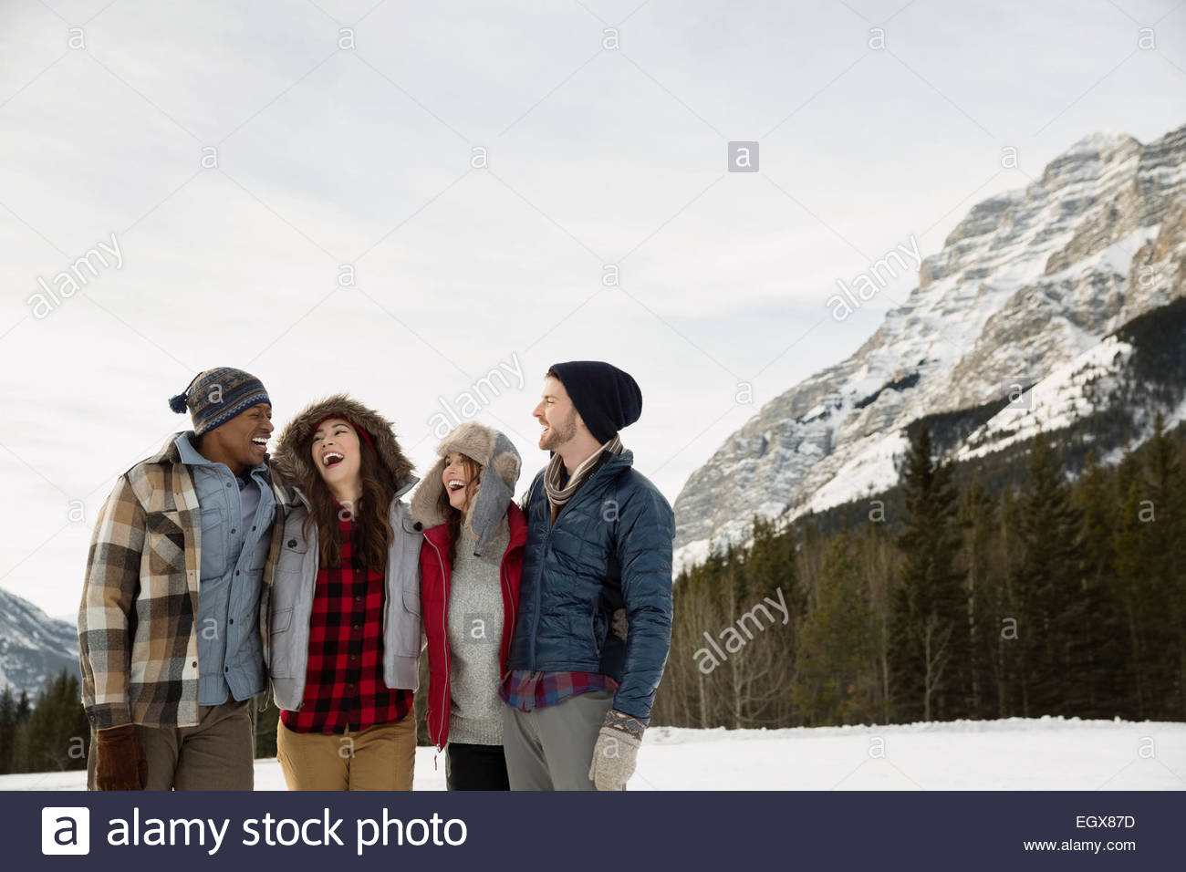 Couples laughing below snowy mountain - Stock Image