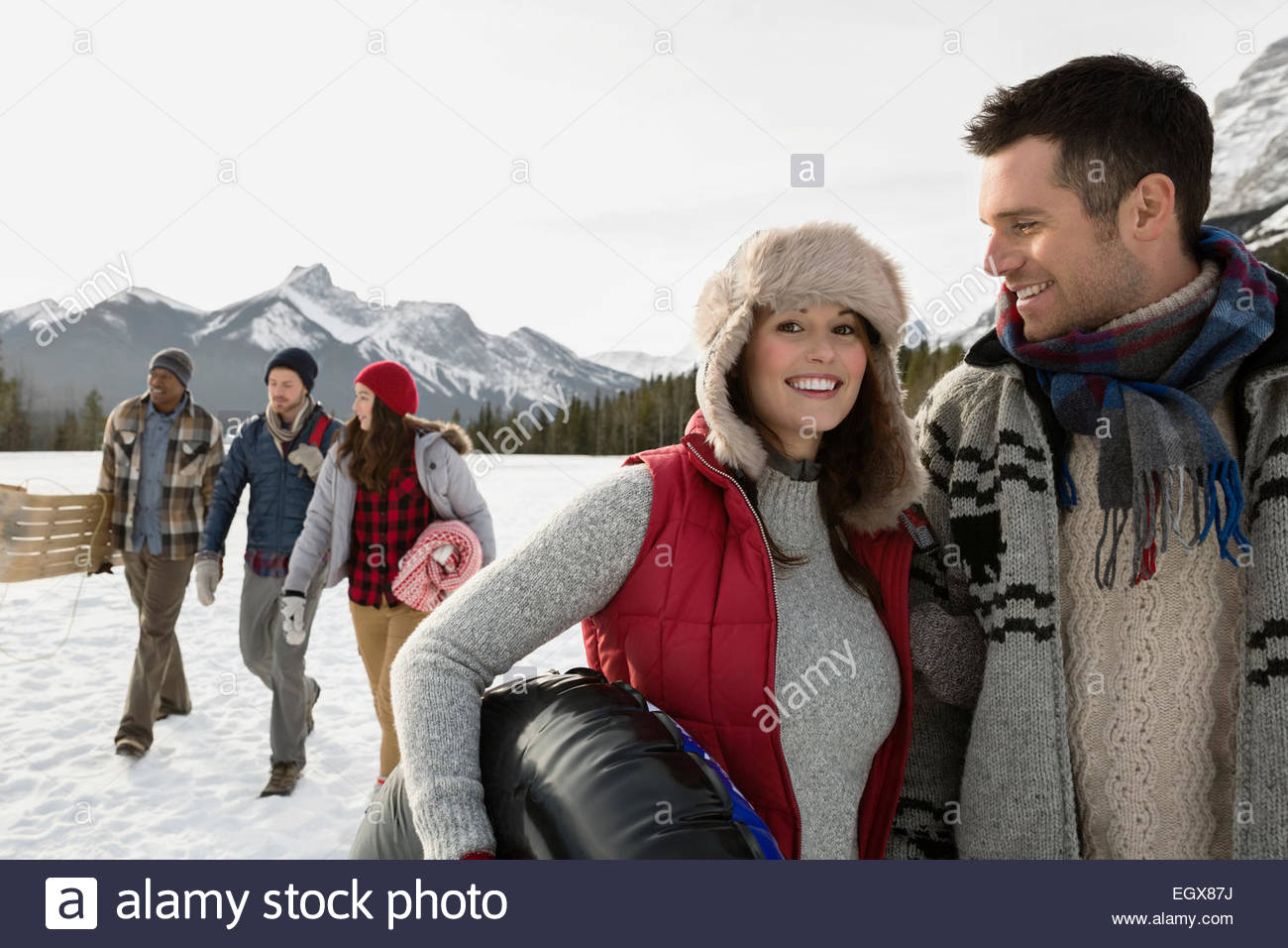 Smiling couple in snowy field below mountains - Stock Image