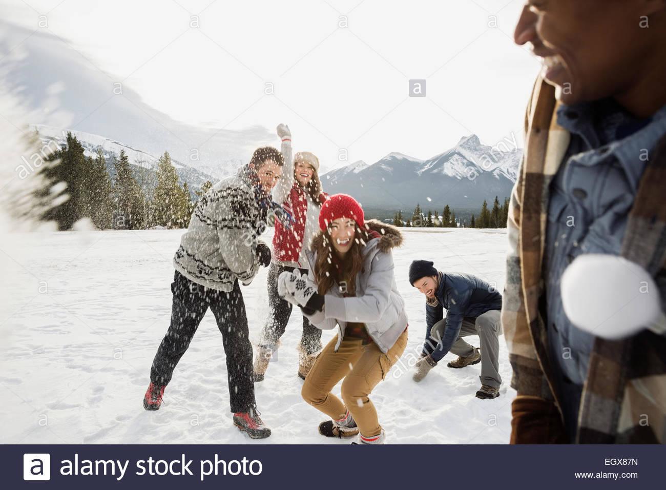 Friends enjoying snowball fight in field below mountains - Stock Image