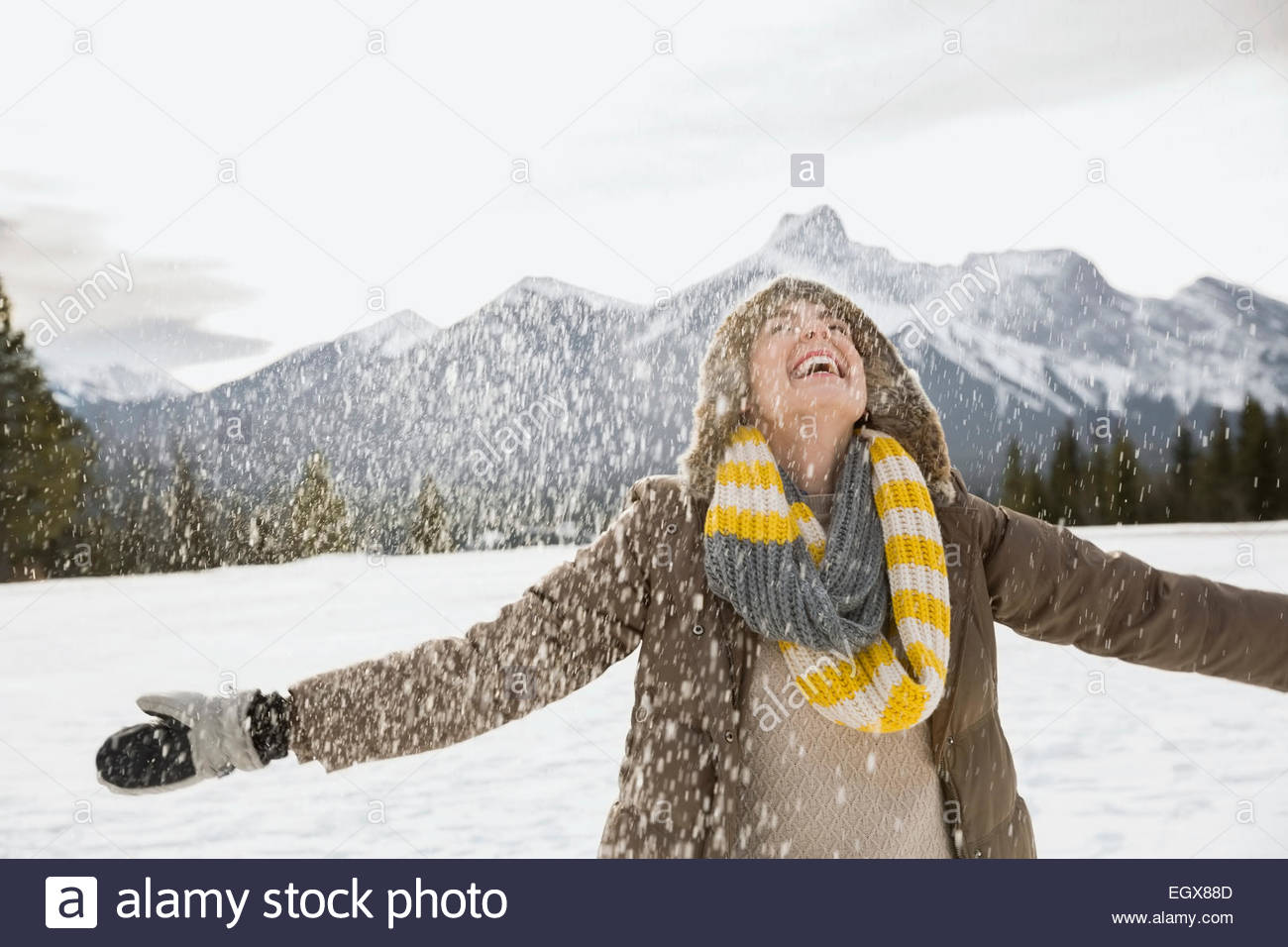 Snow falling around exuberant woman with arms outstretched - Stock Image