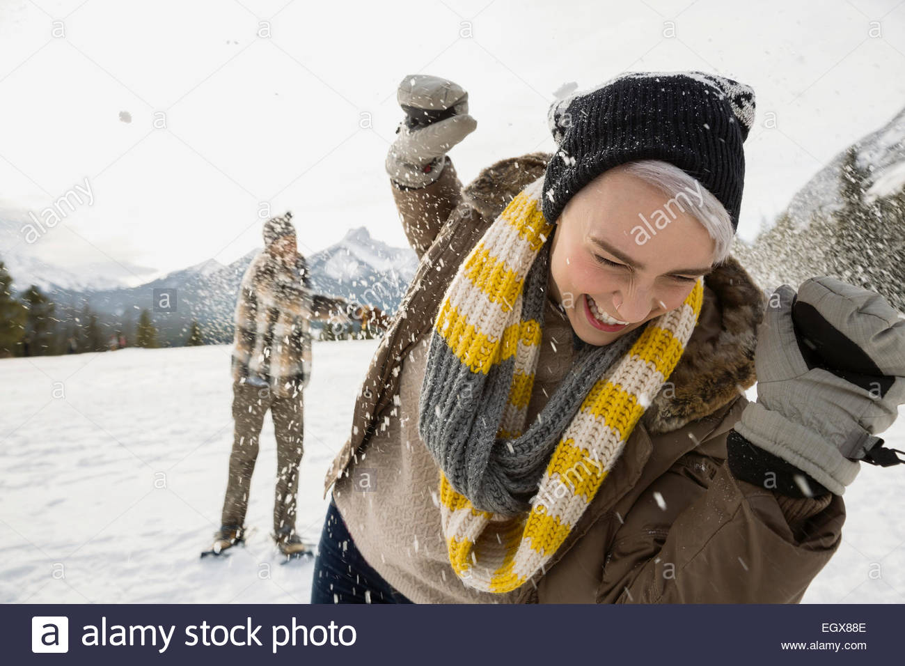 Couple enjoying snowball fight in field below mountains - Stock Image