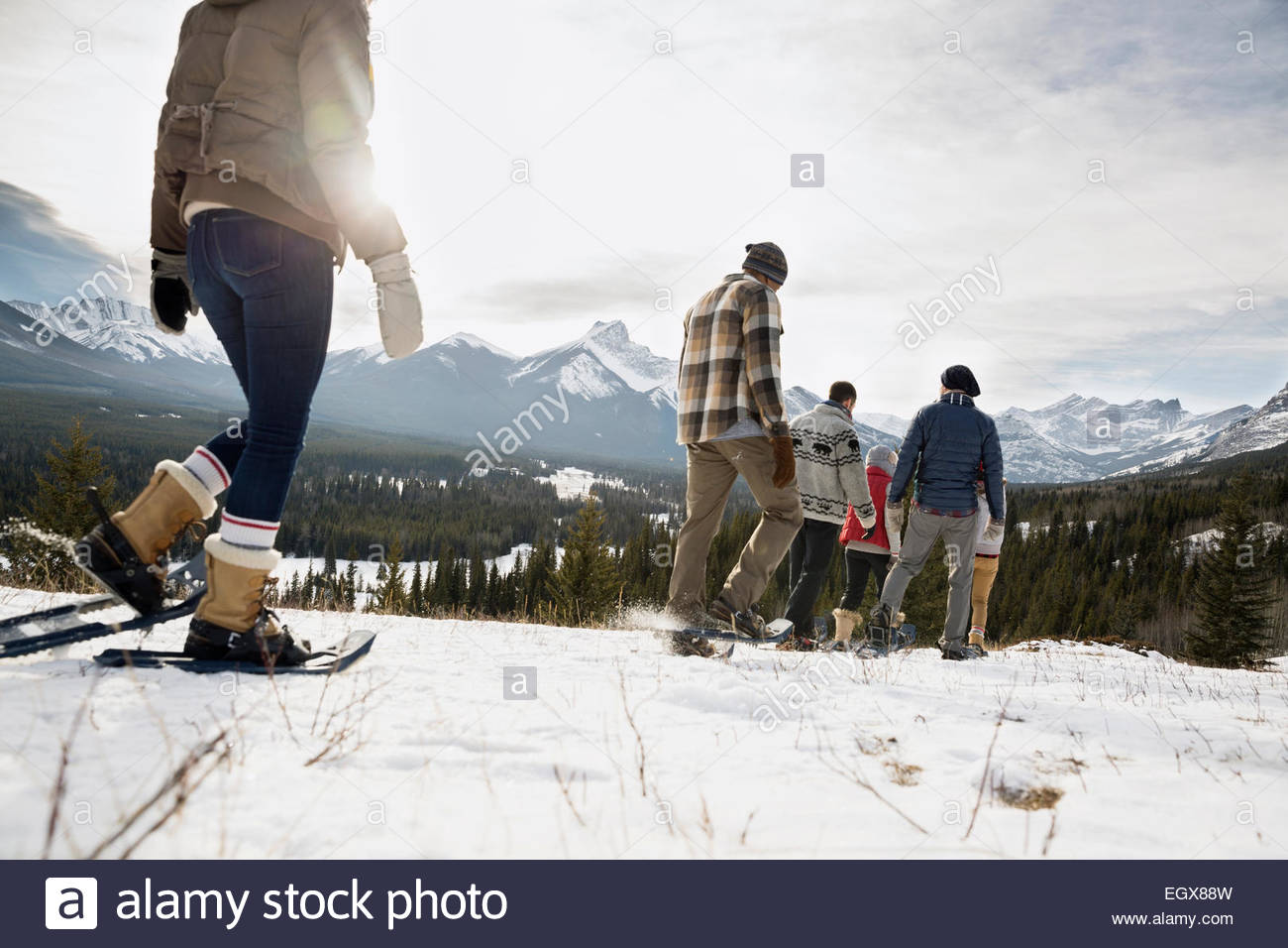 Friends snowshoeing below snowy mountains - Stock Image