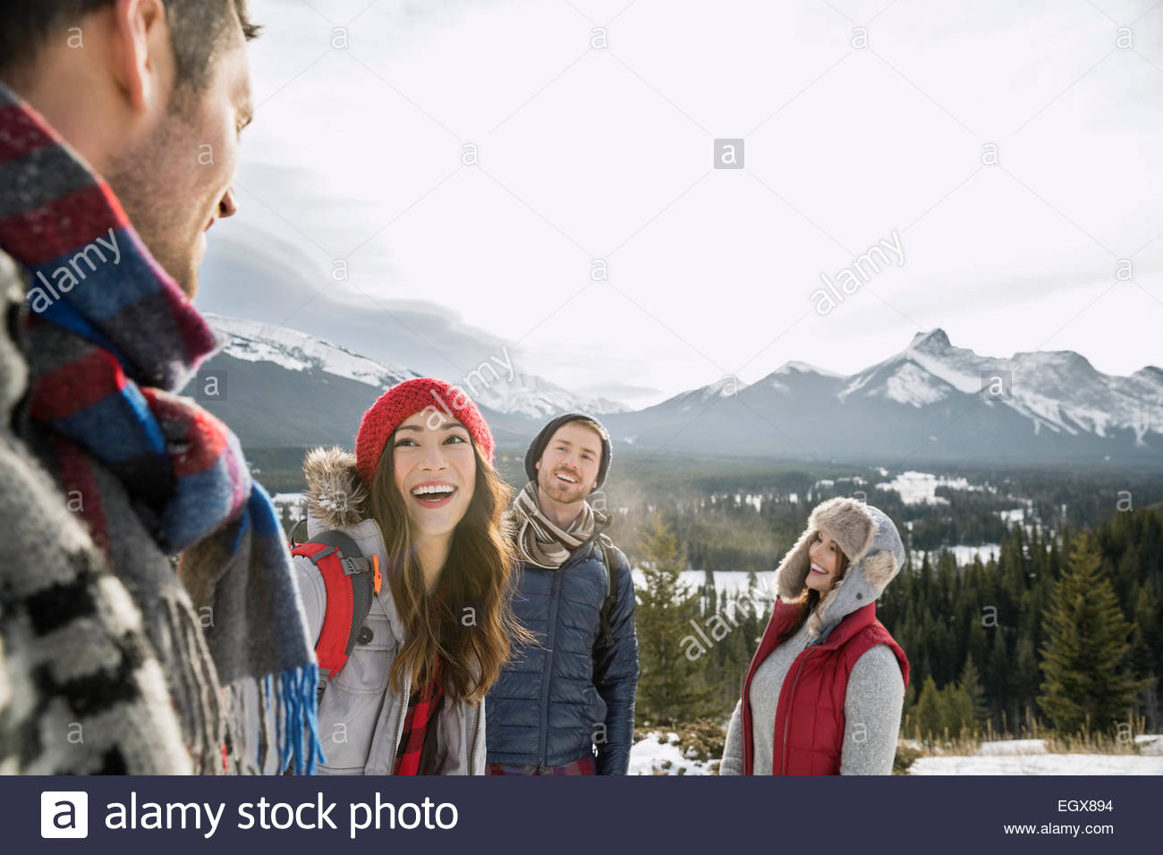 Friends laughing below snowy mountains - Stock Image