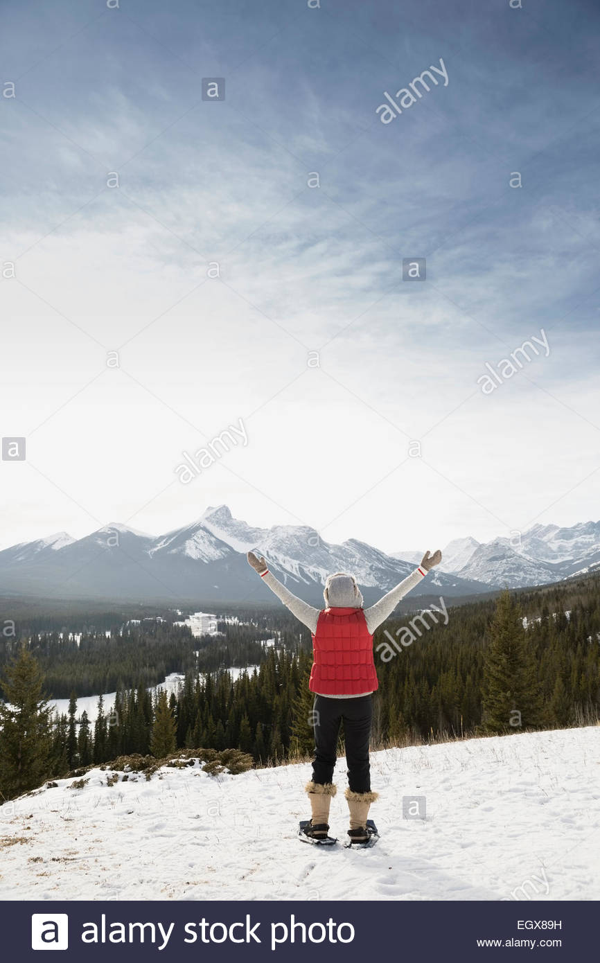 Exuberant woman snowshoeing and facing snowy mountains - Stock Image