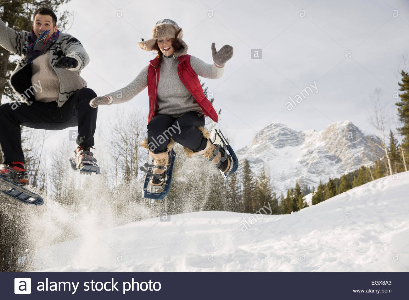 Couple jumping in snowshoes below snowy mountain - Stock Image