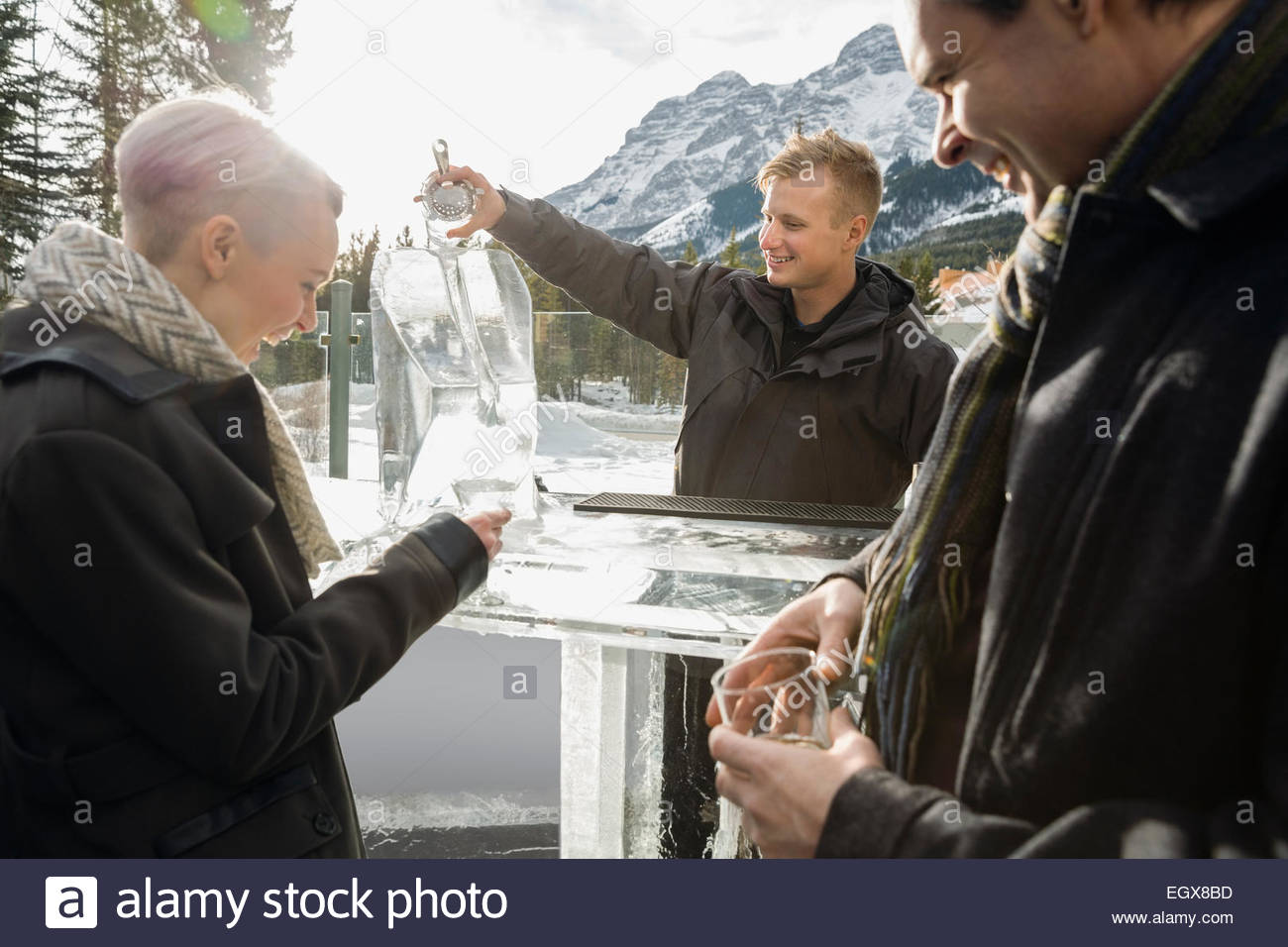 Bartender chipping at ice block on outdoor patio - Stock Image