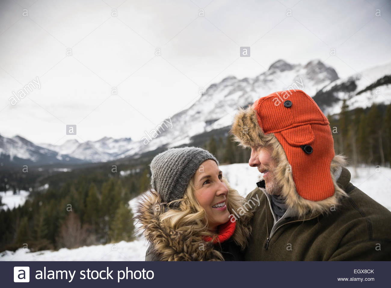 Couple smiling below snowy mountains - Stock Image