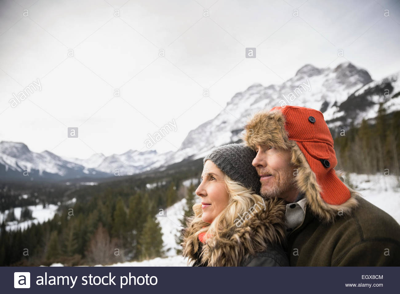 Serious couple looking away below snowy mountains - Stock Image