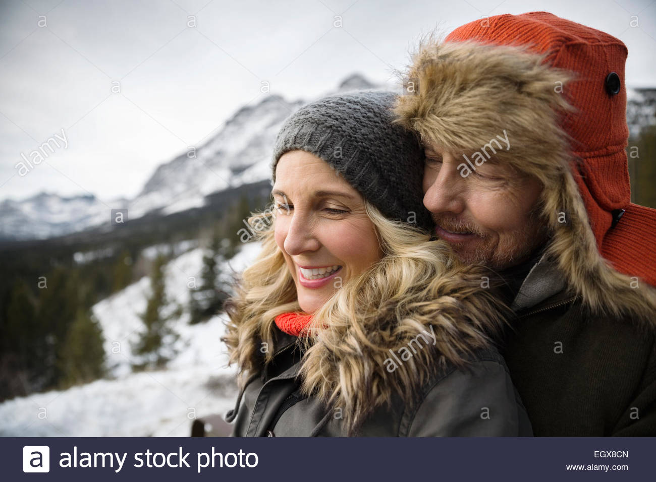 Couple in warm clothing hugging below snowy mountain - Stock Image