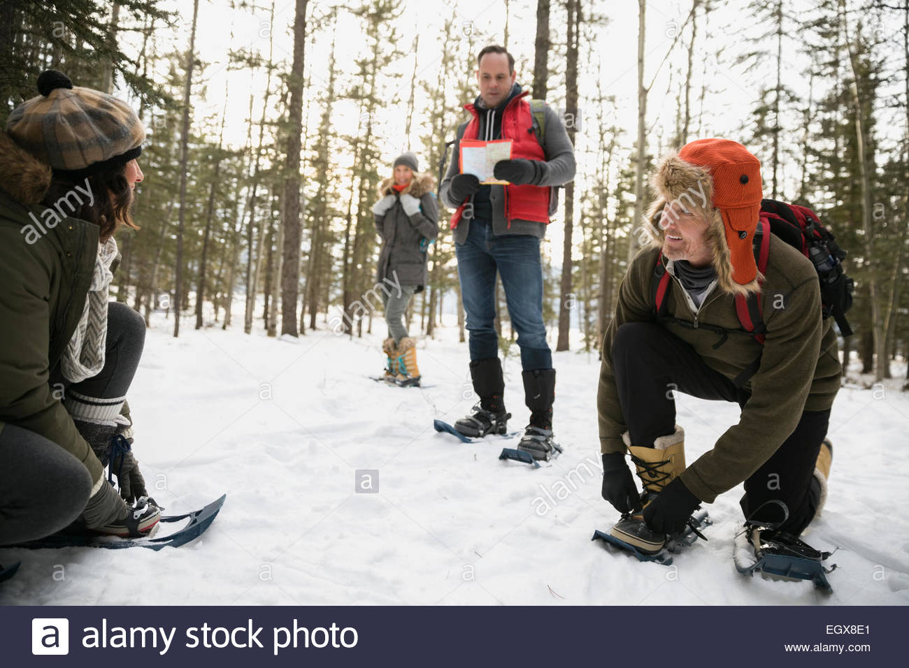 Friends putting on snowshoes in snowy woods - Stock Image