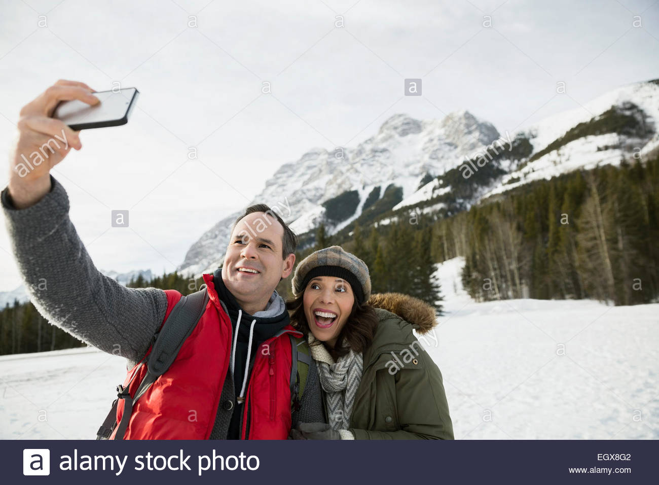 Couple taking selfie below snowy mountains - Stock Image