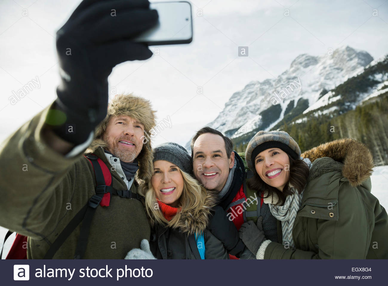Couples taking selfie below snowy mountains - Stock Image