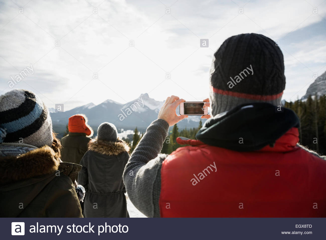 Man with camera phone photographing snowy mountains - Stock Image