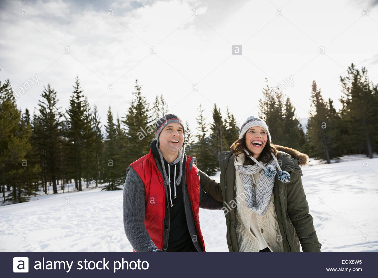 Smiling couple walking in snowy field - Stock Image