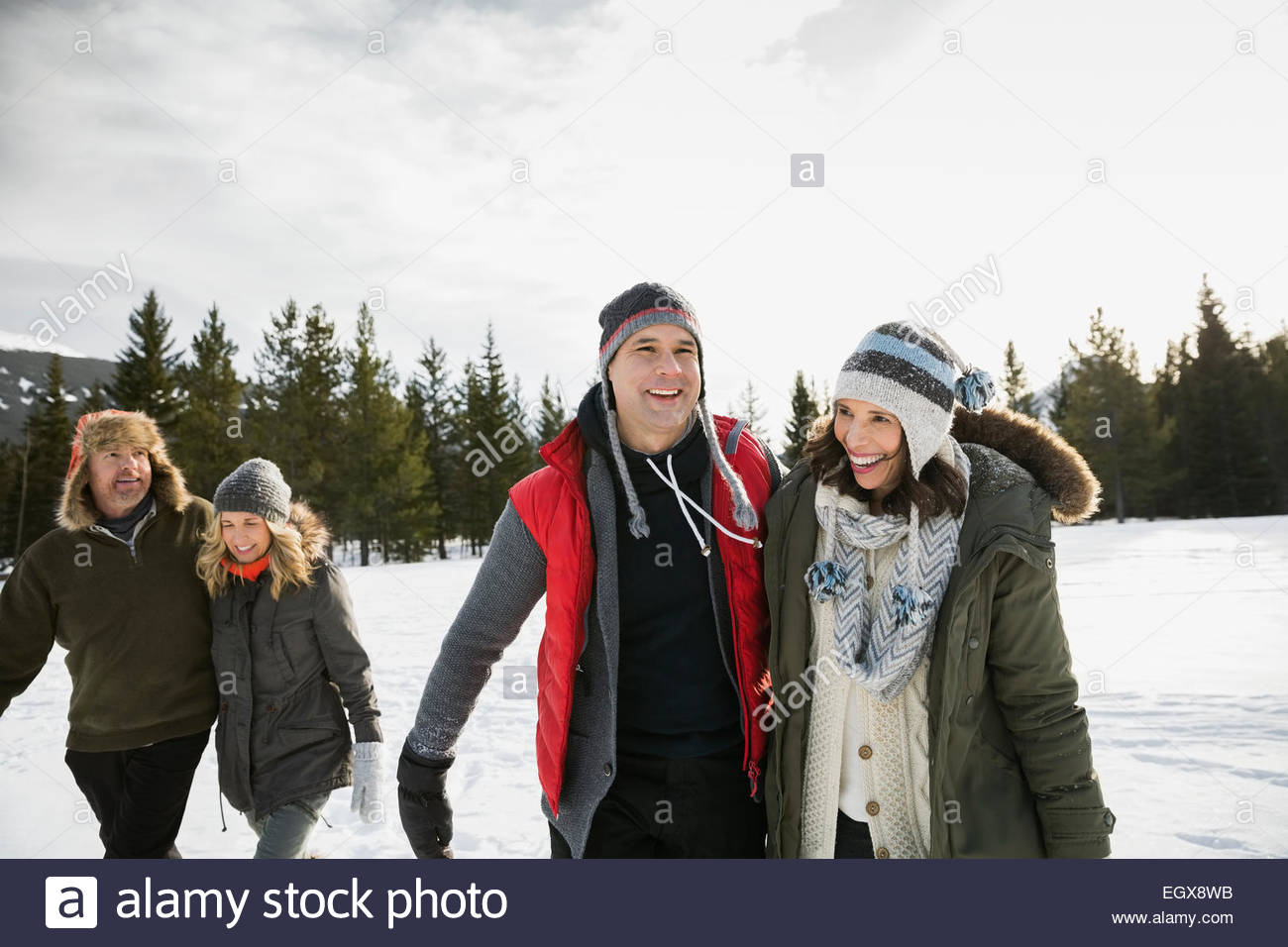 Smiling couples walking in snowy field - Stock Image