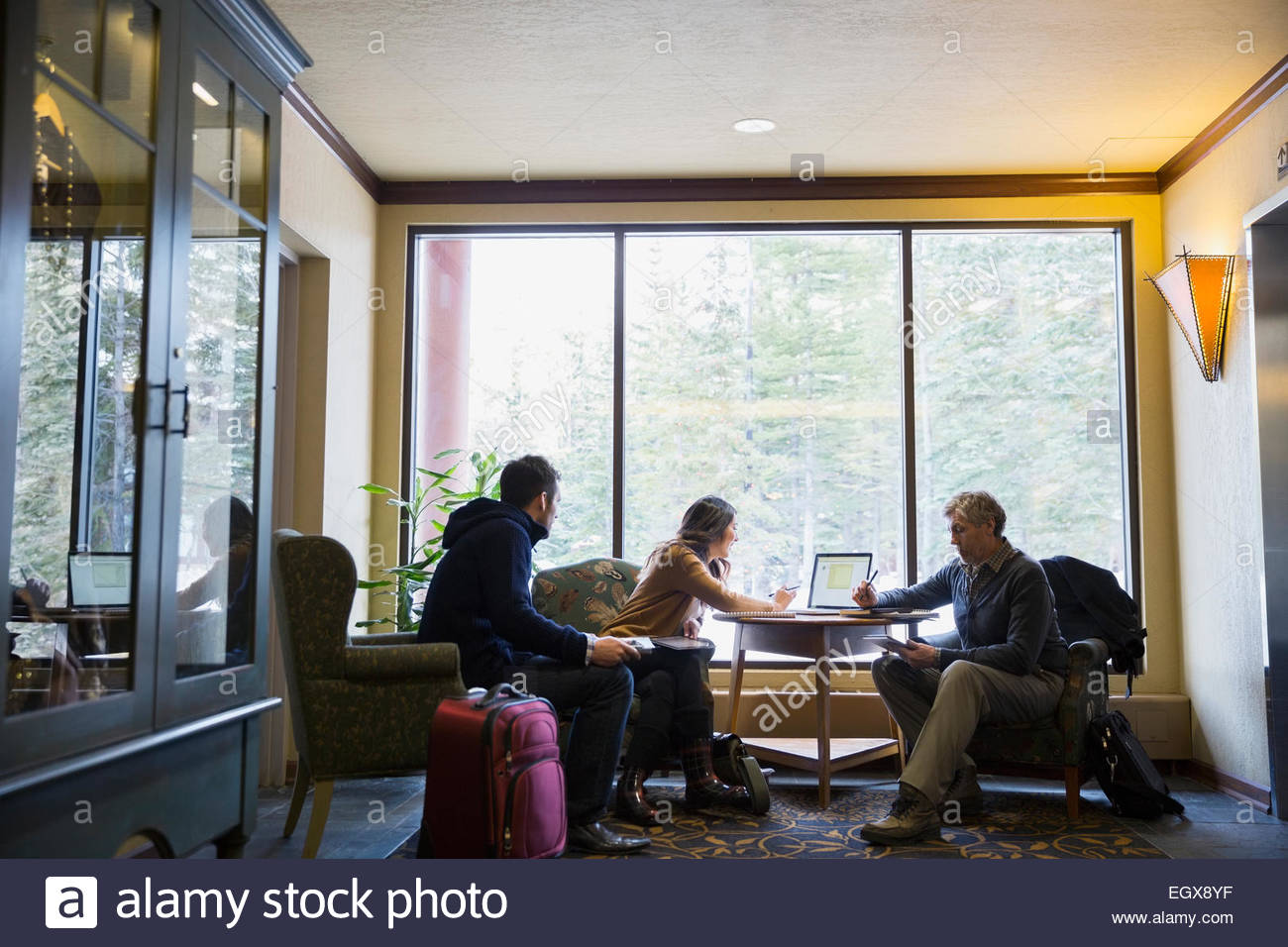 Business people working at laptop in lobby Stock Photo
