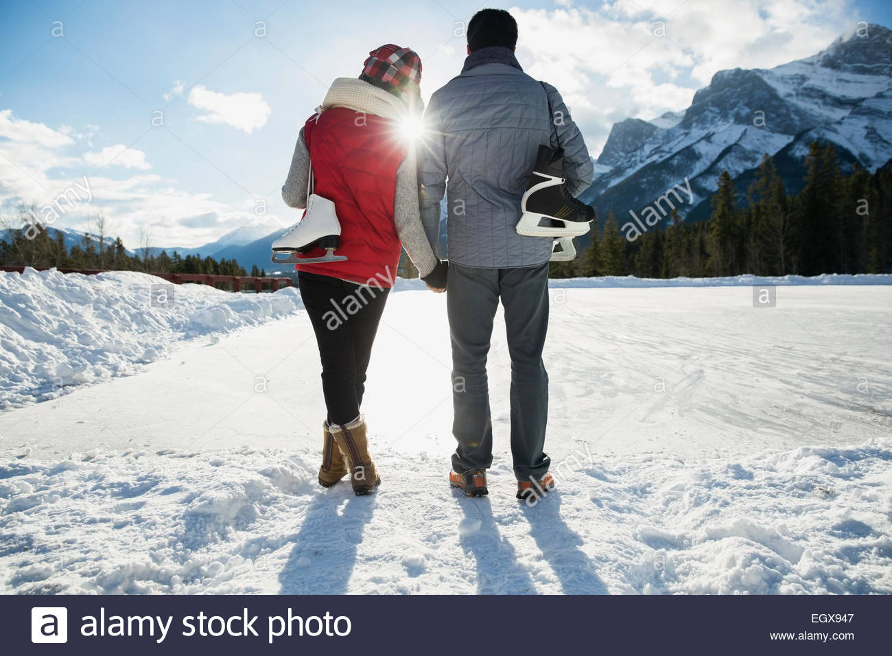 Couple with ice skates hugging below snowy mountain - Stock Image