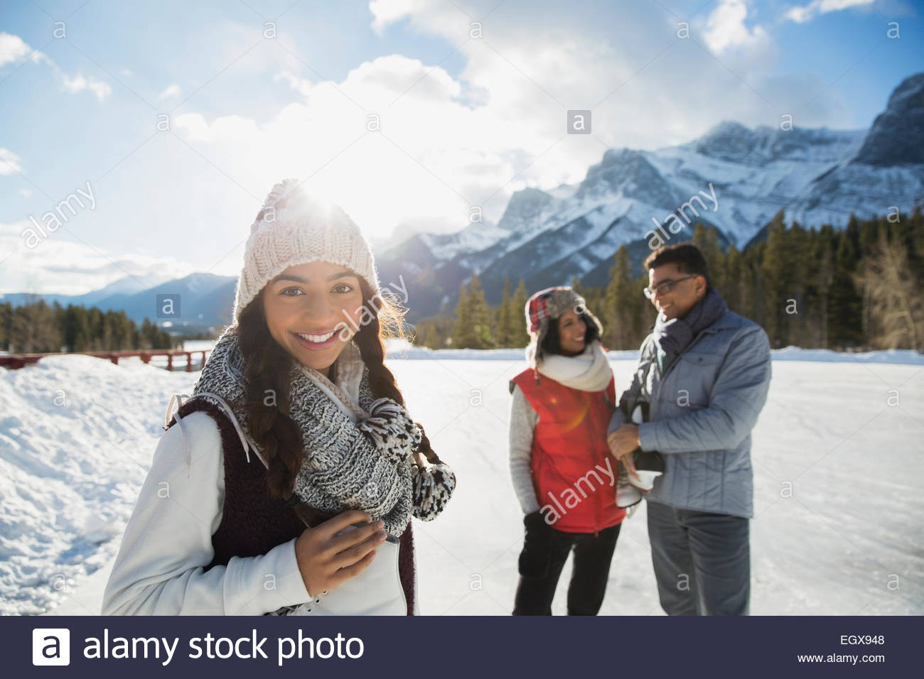 Portrait of smiling teenage girl below snowy mountain - Stock Image