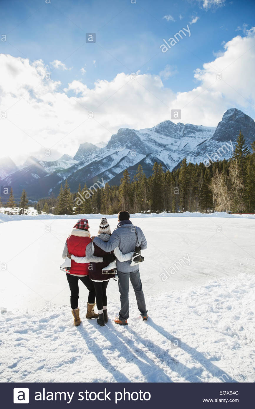 Family with ice skates hugging below snowy mountain - Stock Image