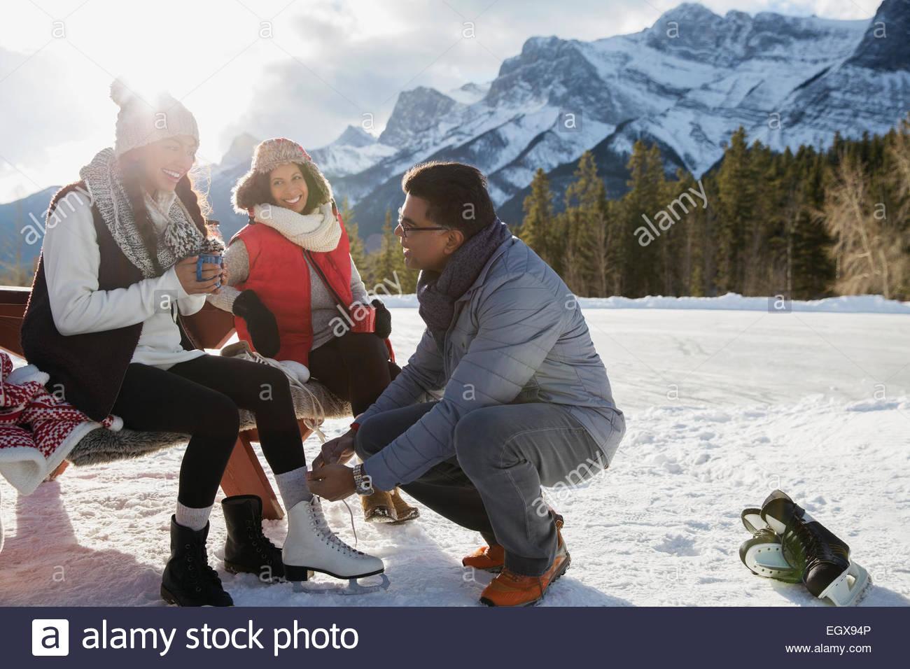 Family putting on ice skates below snowy mountain - Stock Image