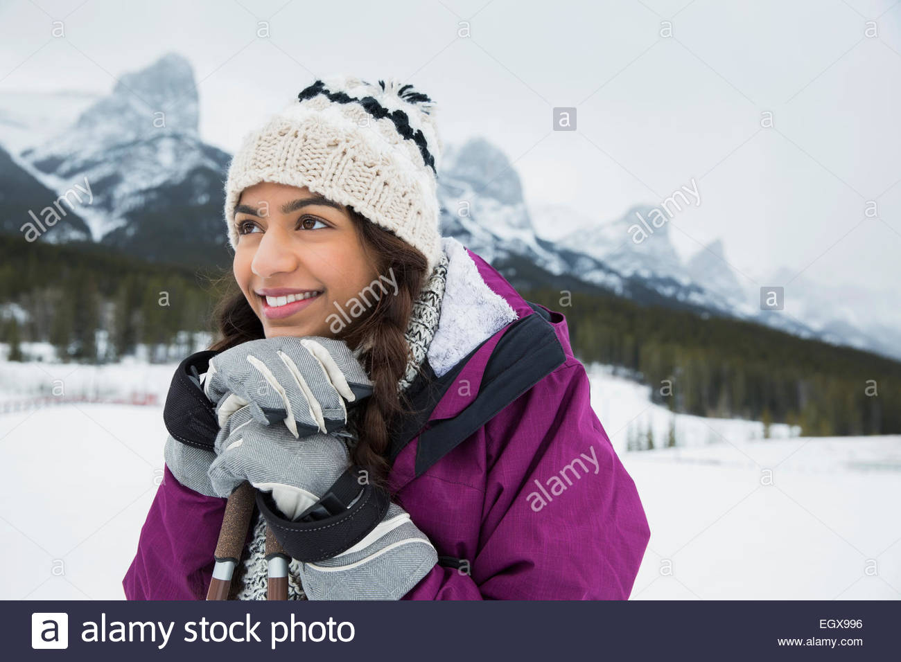 Smiling girl with ski poles below snowy mountains - Stock Image