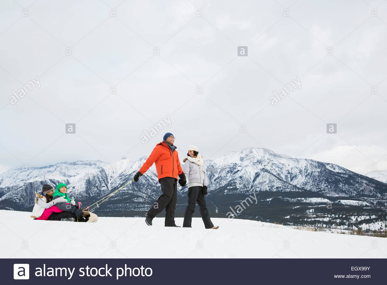 Parents pulling children on sled in snowy field - Stock Image