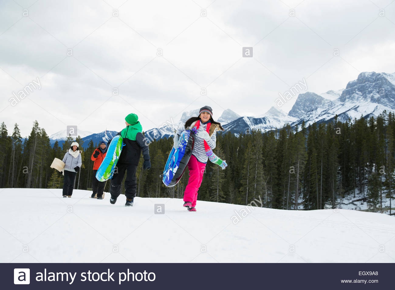 Family with inner tubes in snowy field - Stock Image