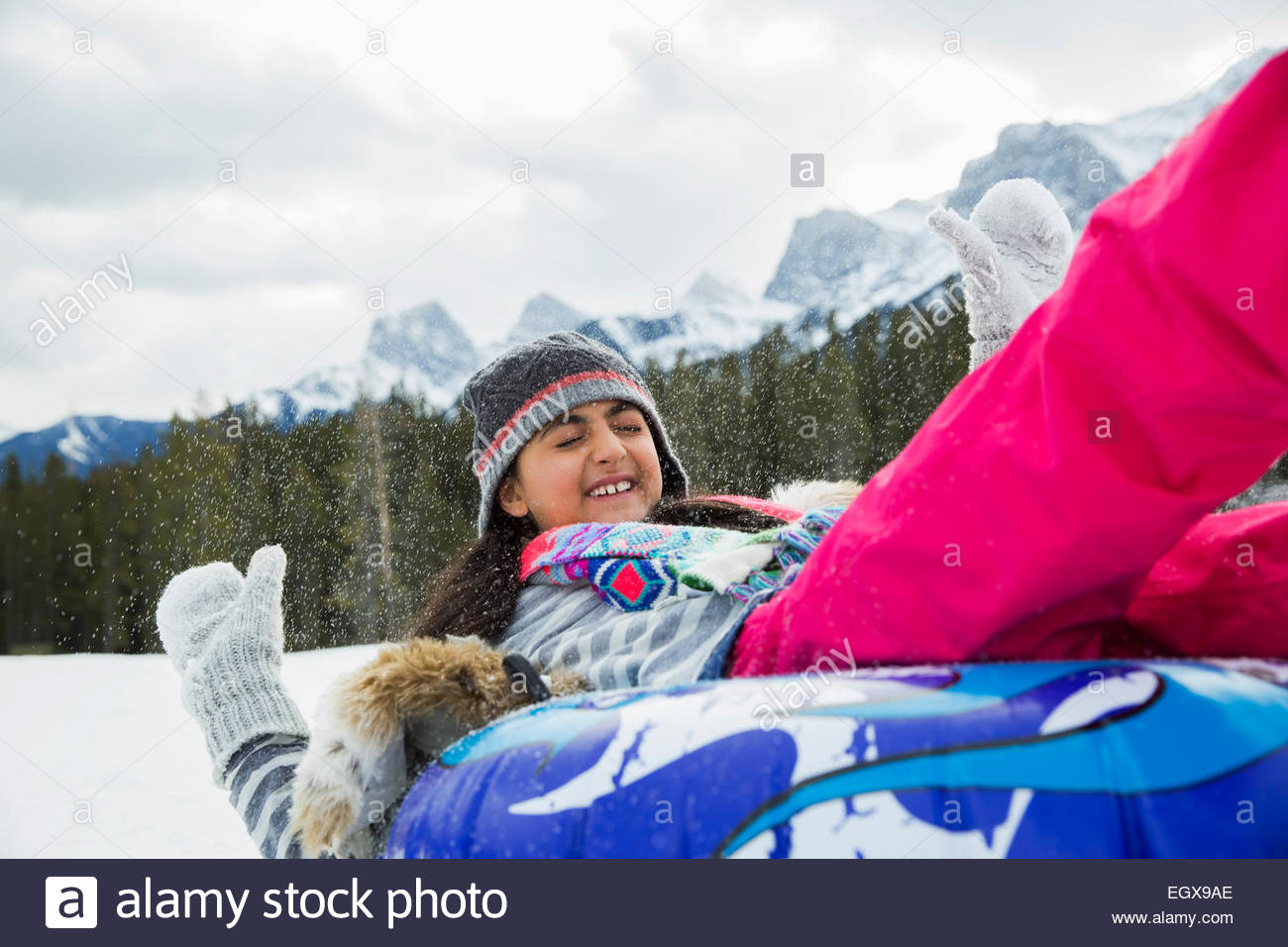 Girl playing on inner tube in snow - Stock Image