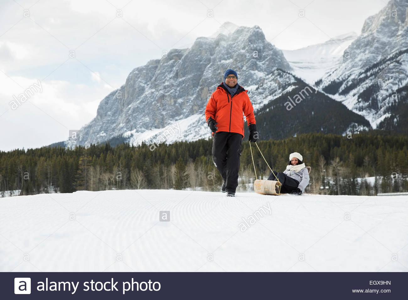 Husband pulling wife on sled in snowy field - Stock Image