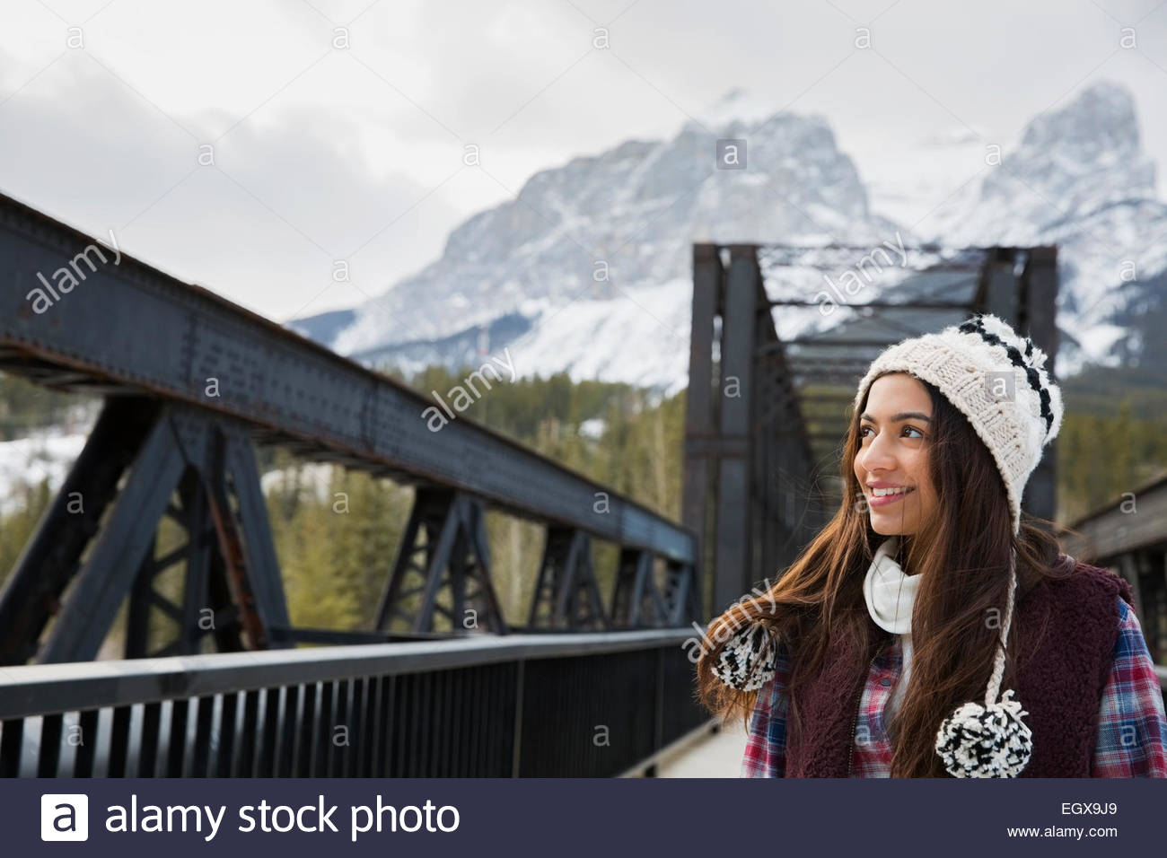 Smiling teenage girl on bridge below snowy mountains - Stock Image