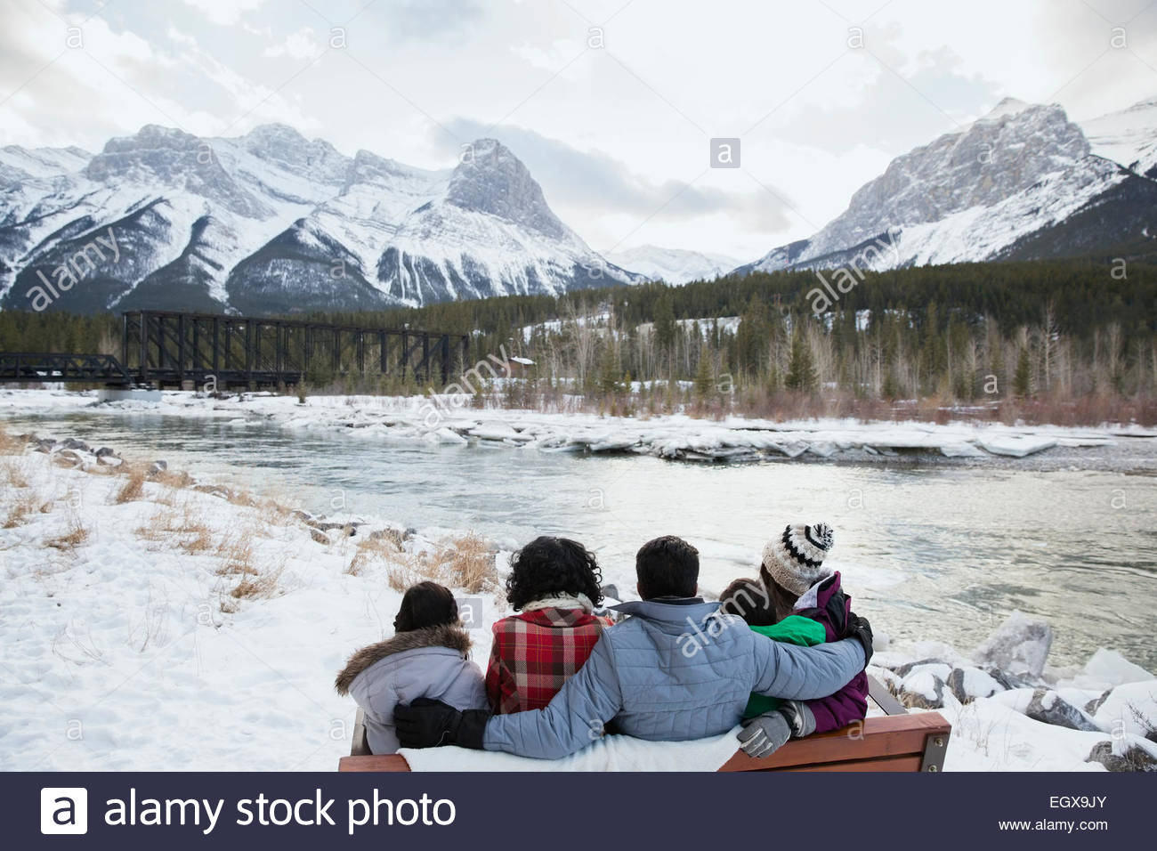 Family on bench at riverside below snowy mountains - Stock Image
