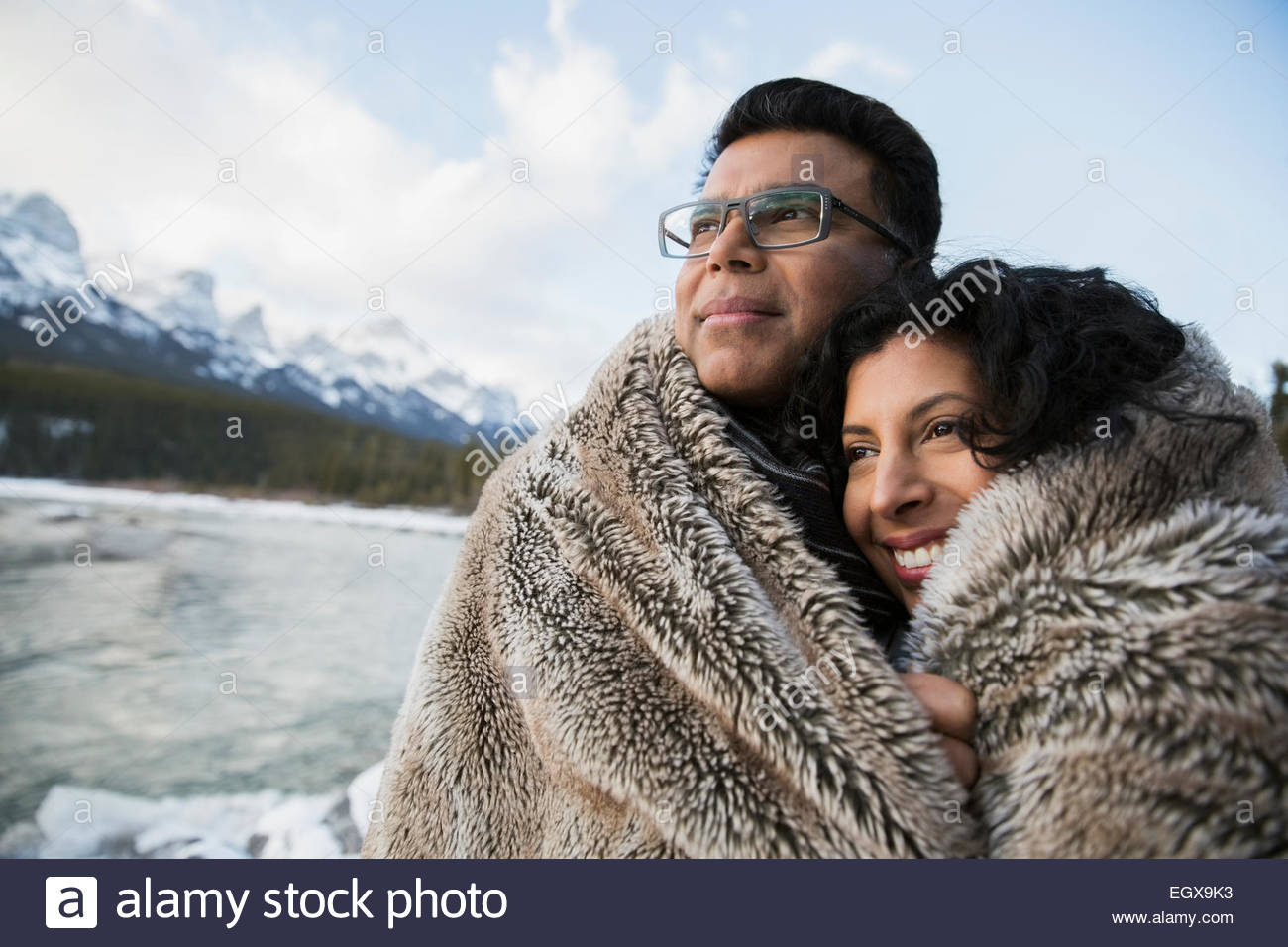 Couple wrapped in blanket at riverside below mountains - Stock Image