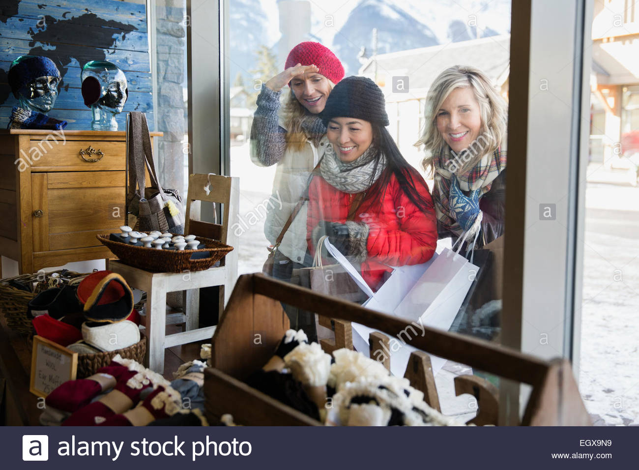 Women in warm clothing window shopping at storefront - Stock Image