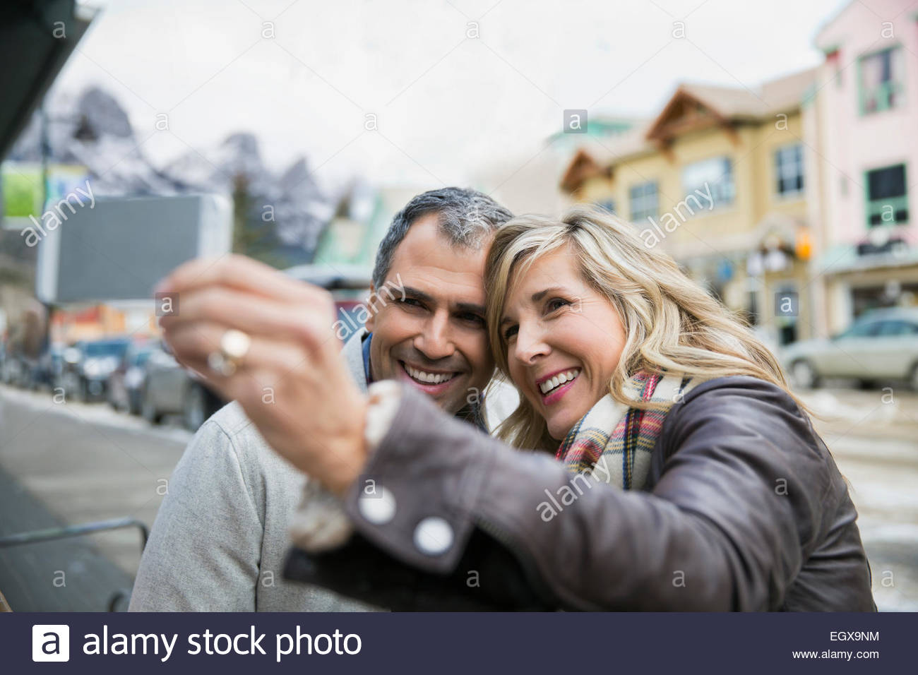 Smiling couple taking selfie outdoors - Stock Image