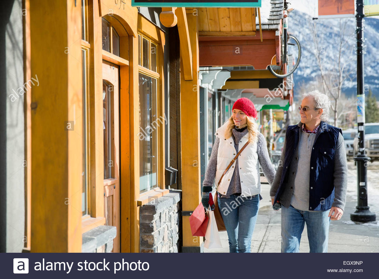 Couple in warm clothing walking along storefront Stock Photo