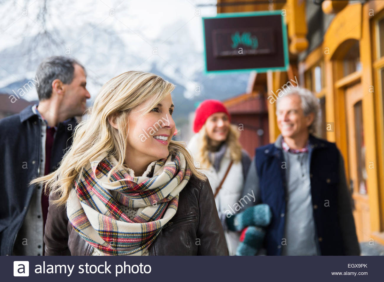 Smiling couples walking along storefronts - Stock Image