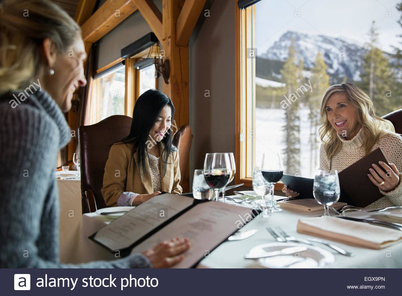 Women looking at menus at restaurant table - Stock Image