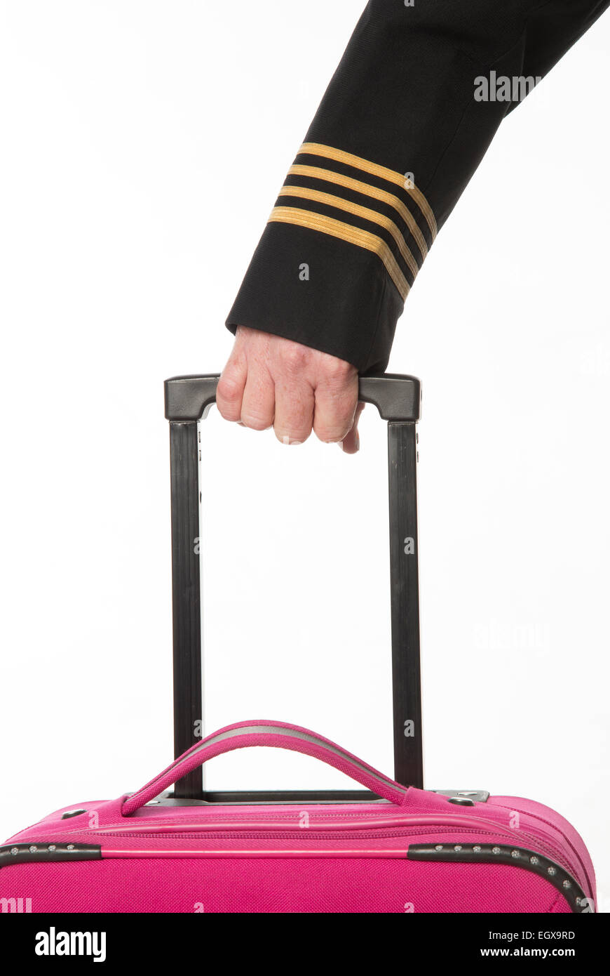 Four gold rings on airline officers uniform wearing gloves and with a carry on bag - Stock Image