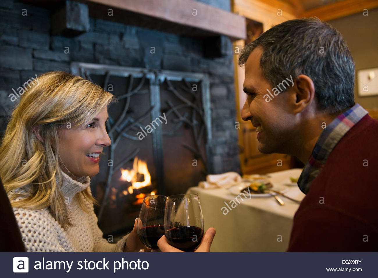 Couple toasting wine glasses at restaurant fireside - Stock Image