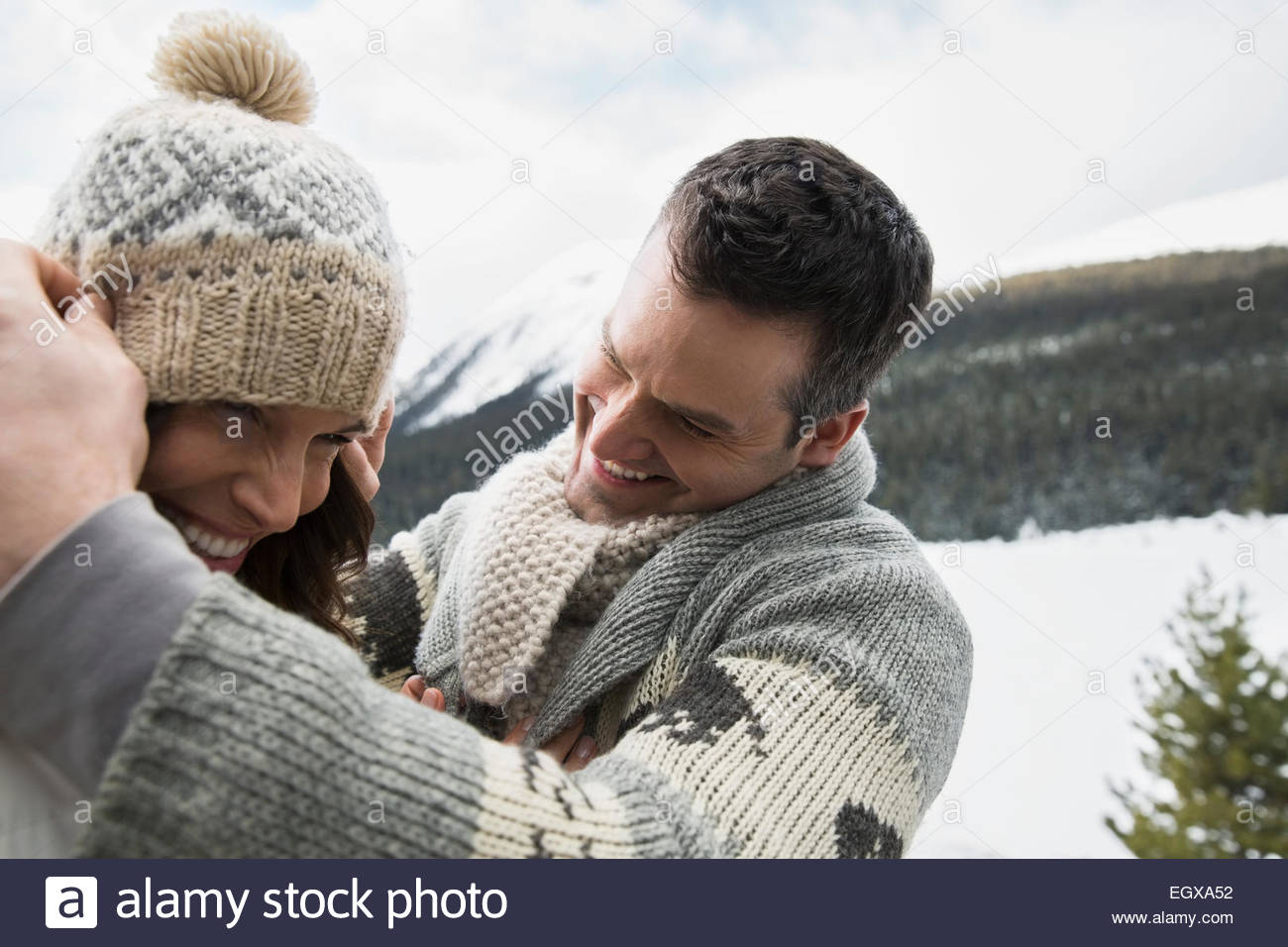 Playful couple wearing warm clothing in snow - Stock Image