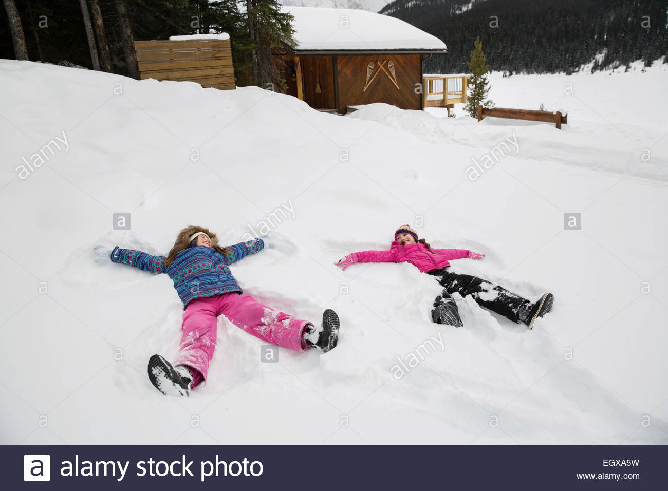 Girls making snow angels in snowy field - Stock Image
