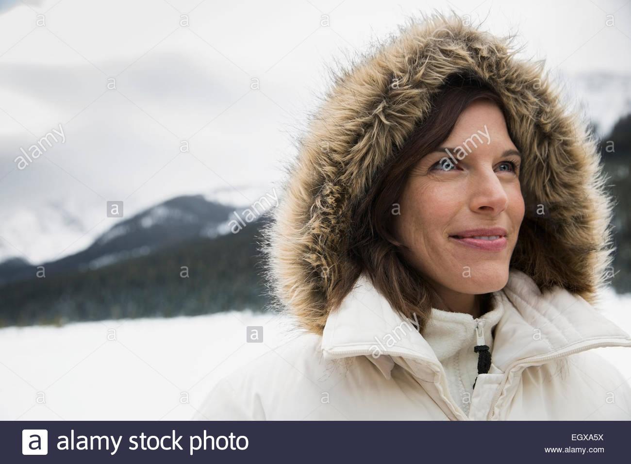 Smiling woman in fur hood in snowy field - Stock Image