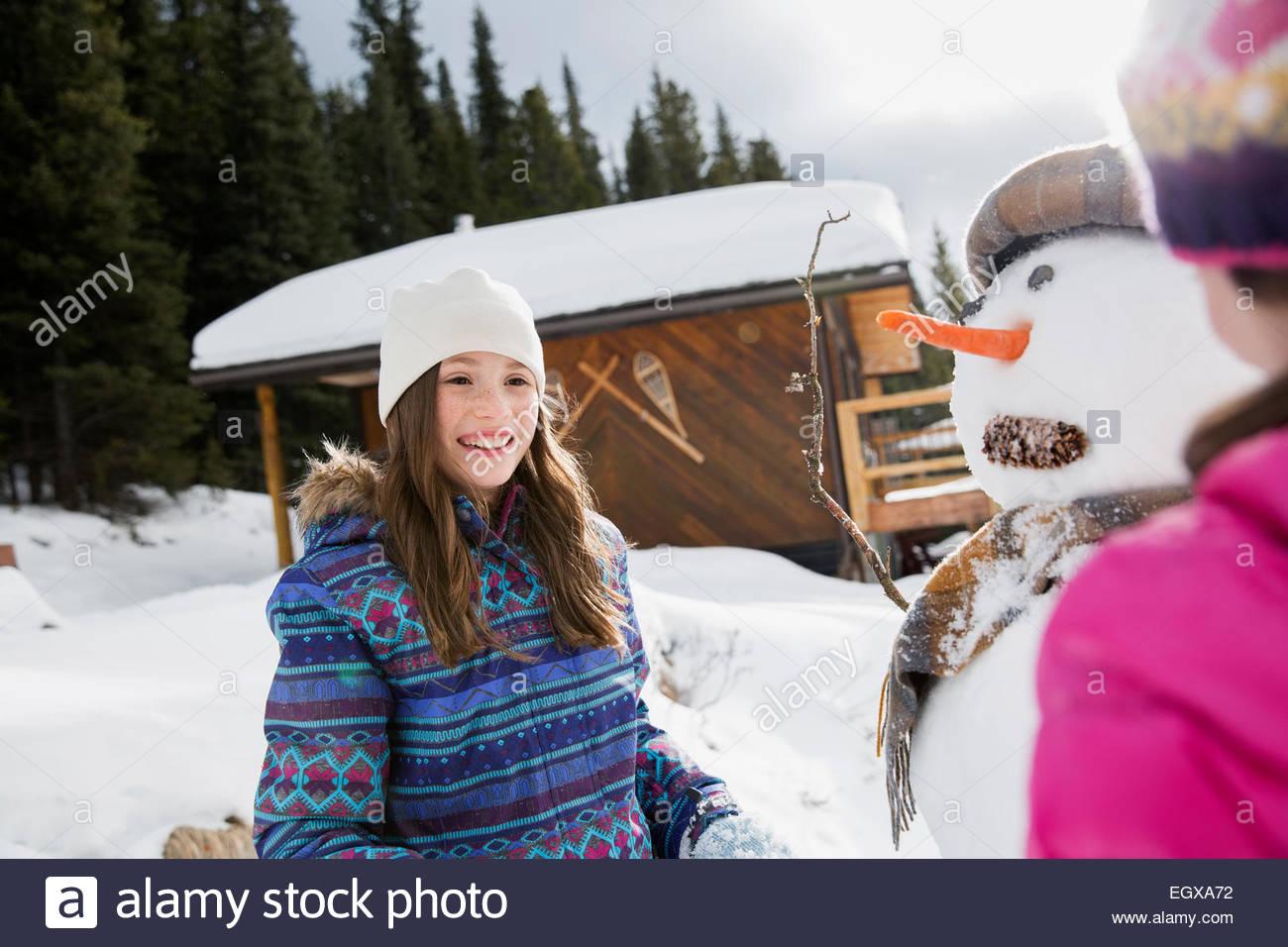 Smiling girl making snowman - Stock Image
