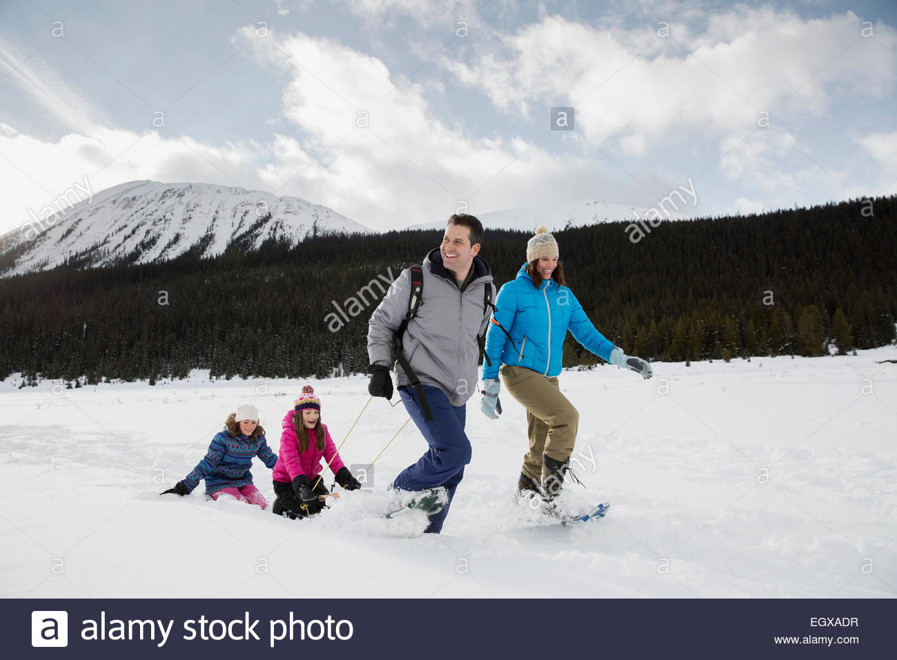 Family sledding in snowy field below mountains - Stock Image