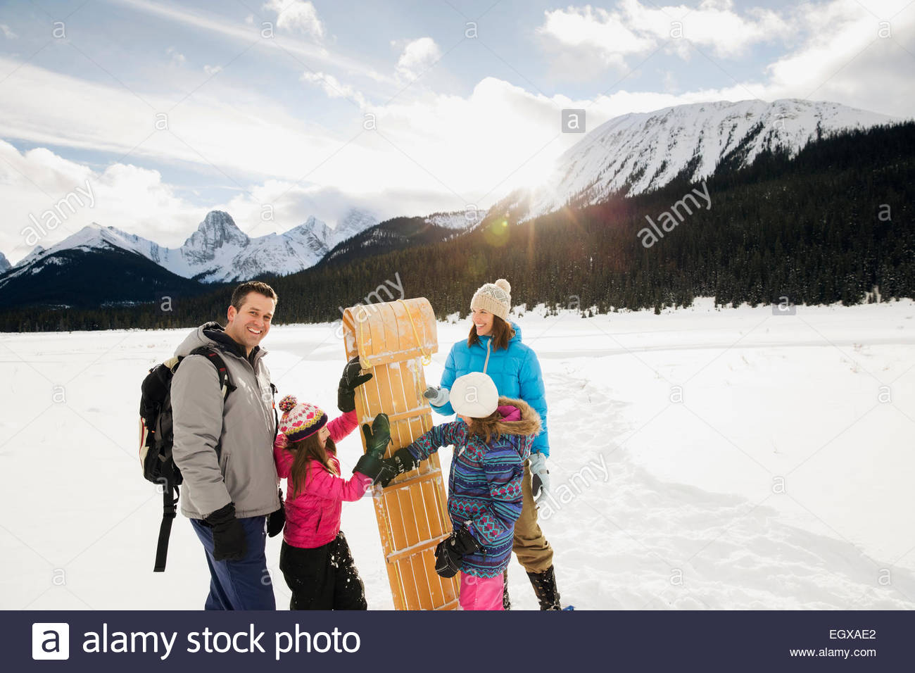 Family with sled in snowy field below mountains - Stock Image